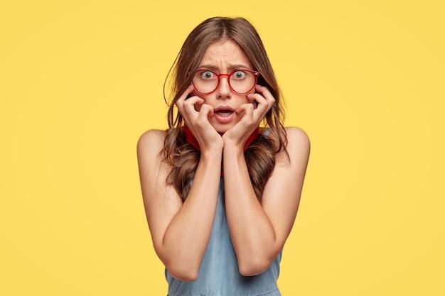 Обеспокоенная, нервная застенчивая женщина держит руки за щеки, смотрит с испуганным выражением лица, носит оптические очки, чувствует беспокойство как совершенную ошибку, с неуверенным выражением лица, изолирована на желтой стене