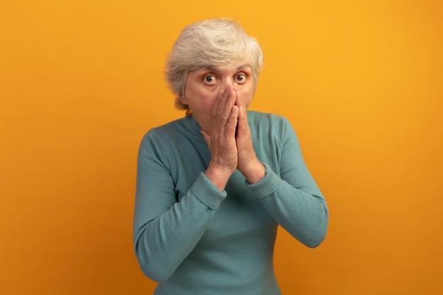 Donna anziana preoccupata che indossa un maglione blu a collo alto che guarda davanti tenendo le mani unite sulla bocca isolata sulla parete arancione con spazio per le copie
