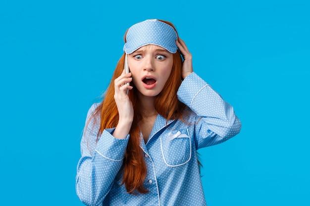 걱정되는 당황하고 불안한 여자는 전화를 받았으며, 나쁜 소식을 발견했으며, 귀 근처에 스마트 폰을 들고, 눈을 터지는 눈 카메라, 머리를 잡고, 놀라고 걱정하는 느낌, 파란색 배경