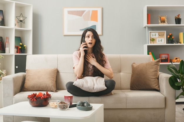 Concerned putting hand on heart young girl speaks on phone sitting on sofa behind coffee table in living room