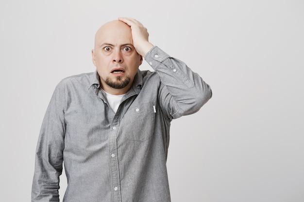 L'uomo calvo perplesso preoccupato tiene la mano sulla testa e fissa confuso