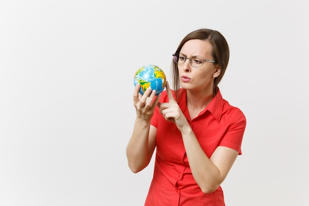 Concerned sad business or teacher woman in red shirt holding in palms earth globe isolated on white background. problem of environmental pollution. stop nature garbage, environment protection concept.