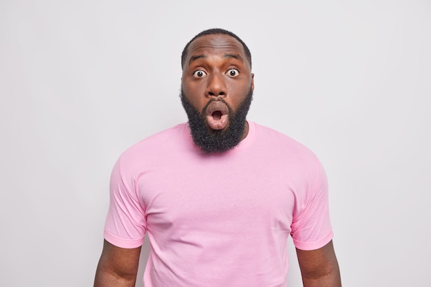 Concerned shocked bearded man stares bugged eyes at front opens mouth in amazement reacts on surprising news dressed in casual pink t shirt isolated over white wall