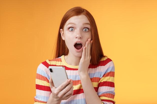 걱정되는 충격적인 감정적 인 빨간 머리 소녀는 놀라운 뉴스 모습 카메라 드롭 턱 헐떡이며 감동적인 터치 뺨을 잡고 스마트 폰 마무리 인상적인 불안한 이야기, 주황색 배경을 읽습니다.