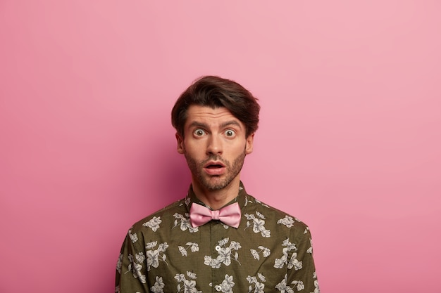 Обеспокоенный шокированный европейский мужчина с выражением лица смотрит в камеру, задыхается от ужасных новостей, одетый в модную рубашку.