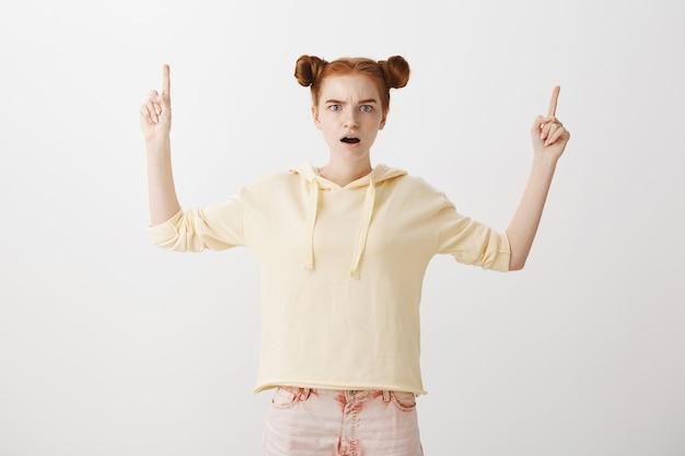 Обеспокоенная шокированная рыжая девушка показывает пальцами вверх