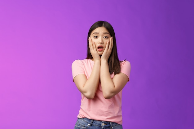 Обеспокоенная шокированная застенчивая неуверенная азиатская женщина, чувствовать себя жалко, стыдно слышать шокирующие новости, хвататься за лицо, жалко друга, задыхаясь, расстроенный открытый рот, обеспокоенно вздыхать, стоять на фиолетовом фоне.