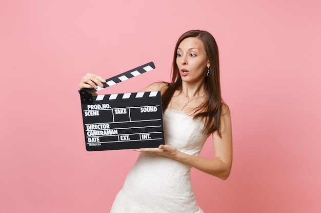 Concerned shocked woman in white dress holding classic black film making clapperboard