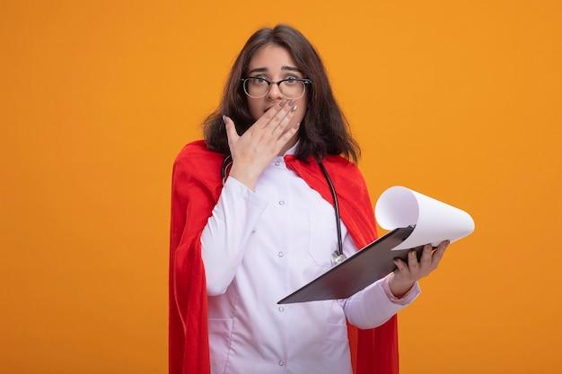 医者の制服と聴診器を身に着けている赤いマントの心配しているスーパーヒーローの女の子は、口に手を置いて正面を見てクリップボードを保持している眼鏡をかけています