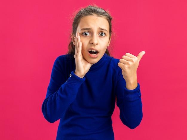 ピンクの壁に隔離された側を指してささやく口の近くに手を保つ心配している10代の少女