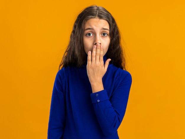 コピースペースでオレンジ色の壁に隔離された口に手を保持している懸念のある10代の少女