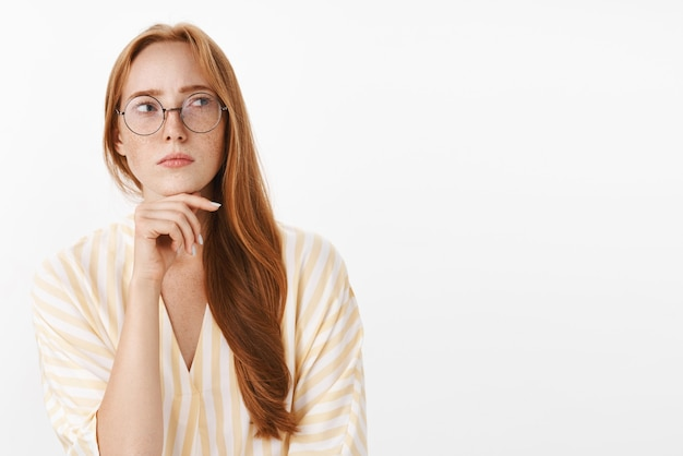 Concerned thoughtful and concentrated creative female writer with red hair and freckles in glasses and trendy yellow blouse standing in hmm pose looking right doubtful and focused touching chin