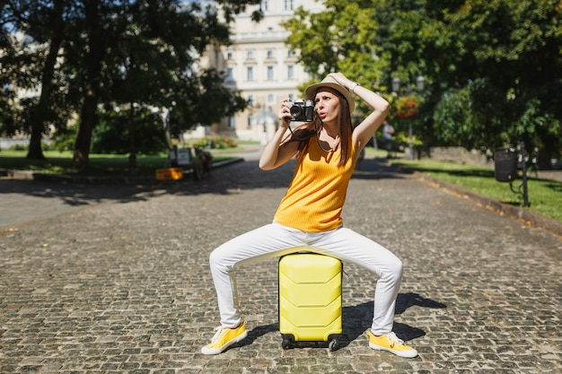 Concerned traveler tourist woman in hat sitting on suitcase take pictures on retro vintage photo camera clinging to head outdoor. girl traveling abroad on weekends getaway. tourism journey lifestyle.