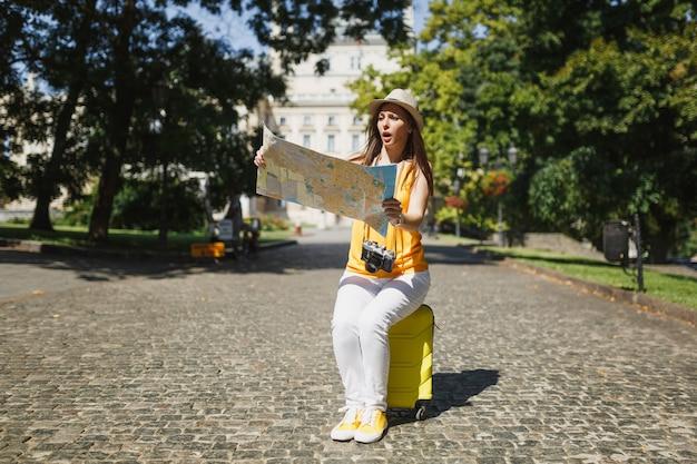 노란 옷 모자를 쓴 걱정스러운 여행자 관광 여성은 도시 야외에서 도시 지도 검색 경로를 보고 있는 여행 가방에 앉아 있습니다. 주말 휴가를 여행하기 위해 해외로 여행하는 소녀. 관광 여행 라이프 스타일.