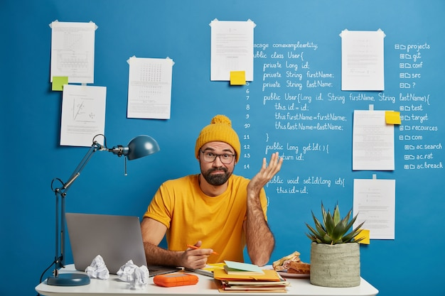 Concerned uncertain male student solves difficult problem while working in study room, writes down on information, makes essay, has lack of idea, wears yellow clothes