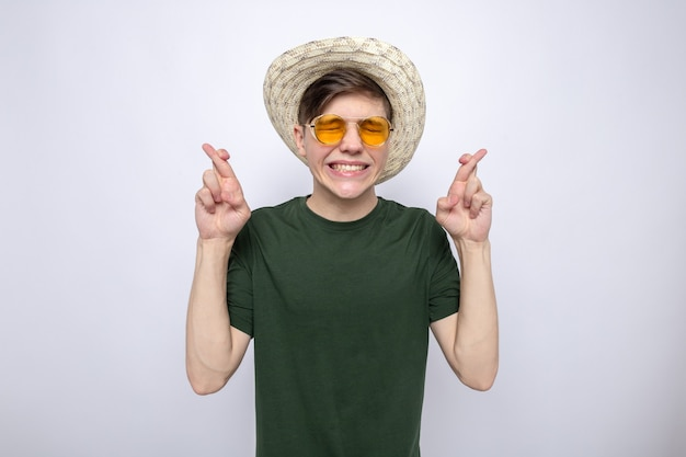 Concerned with closed eyes crossing fingers young handsome guy wearing hat with glasses