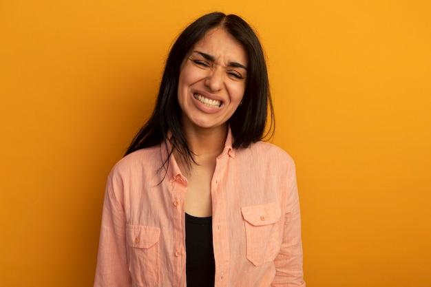 Обеспокоенная закрытыми глазами молодая красивая девушка в розовой футболке изолирована на желтой стене