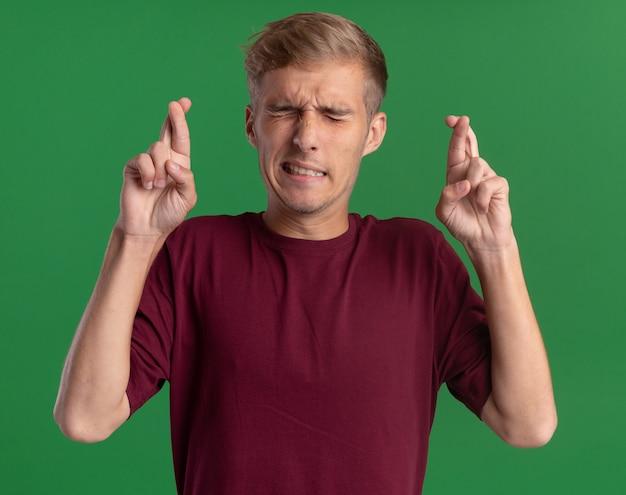 Обеспокоенный с закрытыми глазами молодой красивый парень в красной рубашке, скрестив пальцы на зеленой стене Бесплатные Фотографии