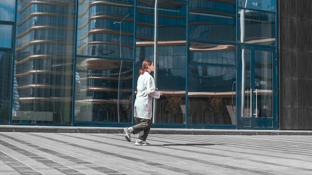 街の建物の近くを走っている心配している女医。コピースペース付きの写真。