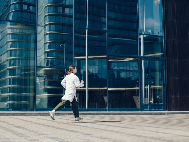 Concerned woman doctor running near a city building