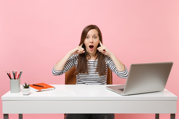 La donna preoccupata non vuole ascoltare coprendosi le orecchie con le dita sedersi e lavorare alla scrivania bianca con un computer portatile contemporaneo