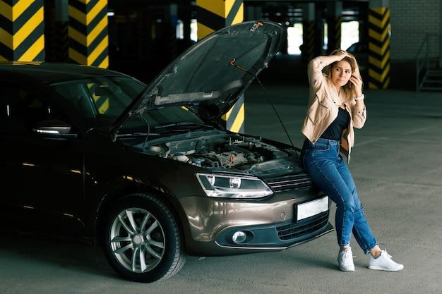 Обеспокоенная женщина-водитель в джинсах и ветровке, вызывающая на парковке помощь с поломкой автомобиля.