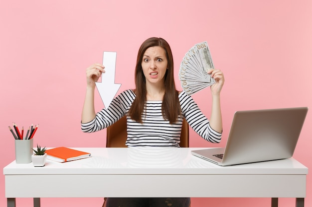 Concerned woman holding down value fall arrow, bundle lots of dollars, cash money work at white desk with pc laptop