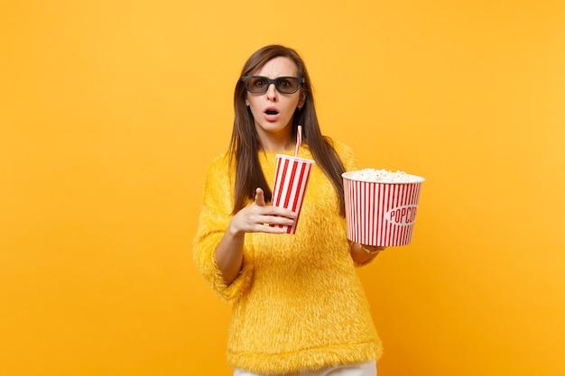 3d 아이맥스 안경을 쓴 걱정스러운 여성이 검지 손가락을 가리키며 노란색 배경에 격리된 팝콘 컵이나 소다 한 컵을 들고 영화를 보고 있습니다. 영화, 라이프 스타일에서 사람들은 진실한 감정.