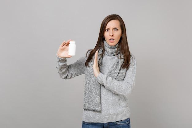 Обеспокоенная женщина в шарфе показывает жест остановки ладонью к таблеткам лекарств, таблеткам аспирина в бутылке, изолированной на сером фоне. здоровый образ жизни, лечение больных, концепция холодного сезона.