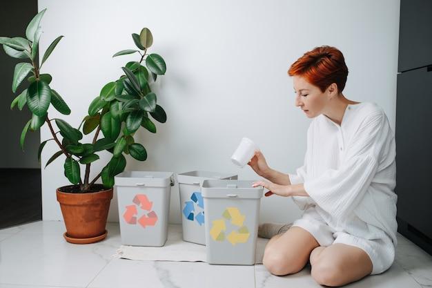 Обеспокоенная женщина сидит на ногах и сортирует мусор между небольшими мусорными баками у себя дома. на них нанесены стрелки разного цвета. держа пластиковый стаканчик.