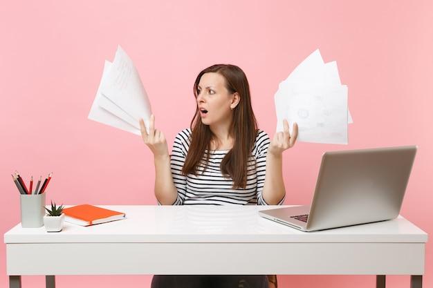 パステルピンクの背景に分離されたラップトップでオフィスに座っている間、紙の文書を保持し、プロジェクトに取り組んでいる心配している女性。業績ビジネスキャリアコンセプト。スペースをコピーします。