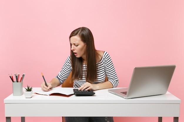 パステルピンクの背景に分離された現代的なpcのラップトップで、計算でメモを書く電卓を使用して心配している女性がオフィスに座って仕事をしています。業績ビジネスキャリアコンセプト。スペースをコピーします。