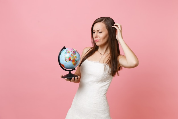 Concerned woman in white dress hold world globe scratching head have problem with choosing place, country, vacation