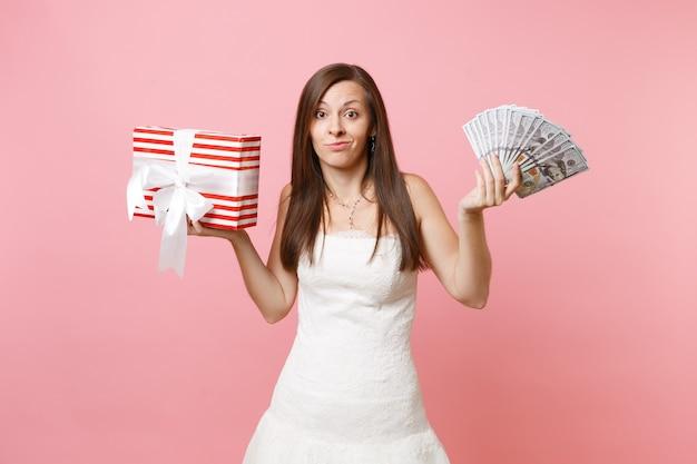 Donna preoccupata in abito bianco che sorride spalmando le mani con un sacco di dollari, denaro contante, scatola rossa con regalo, presente