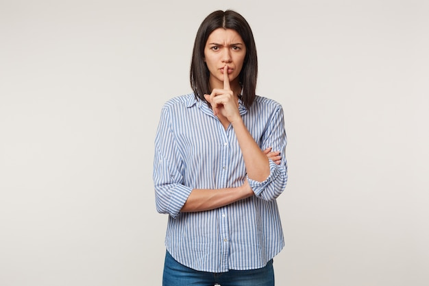 Concerned worried beautiful dark haired girl with swarthy complexion making silence gesture putting fore finger on the lips, asks to stay quiet, keep secret, isolated