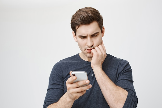 Concerned worried man receive bad news over phone, looking at smartphone display