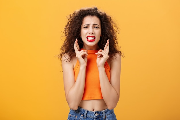 Concerned worried stylish urban girl with curly hairstyle and red lipstick clenching teeth crossing fingers for good luck and frowning feeling nervous and anxious posing troubled over orange wall.