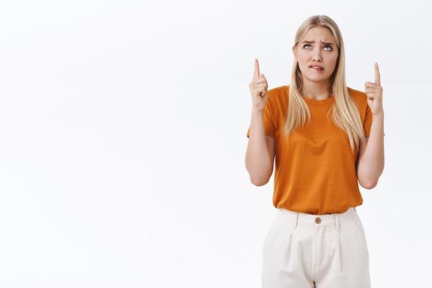 Обеспокоенная, взволнованная молодая симпатичная неуверенная блондинка в оранжевой футболке, штанах, тревожно прикусывающая губу, хмурясь и глядя вверх, указывая на рекламу, нервная, на белом фоне