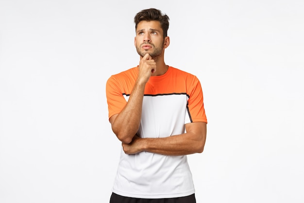 Concerned, worried young handsome male athlete in activewear,