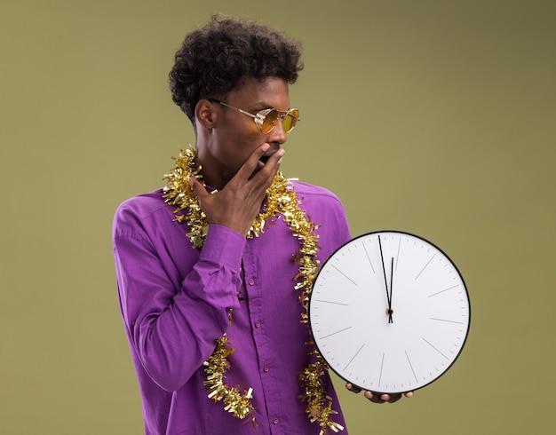 Обеспокоенный молодой афро-американский мужчина в очках с гирляндой из мишуры вокруг шеи, держащий и смотрящий на часы, держа руку на рту, изолированном на оливково-зеленом фоне