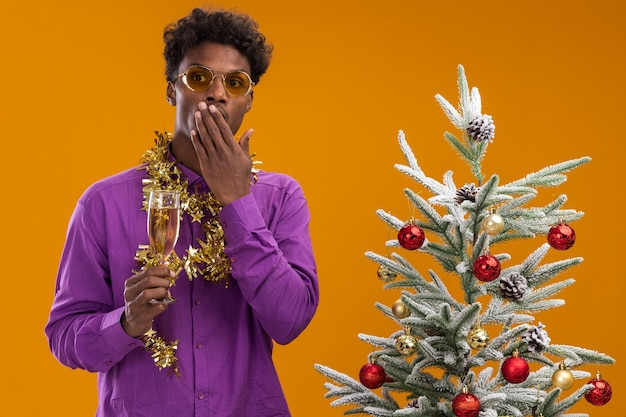 Обеспокоенный молодой афро-американский мужчина в очках с мишурной гирляндой на шее стоит возле украшенной елки и держит за руку бокал шампанского