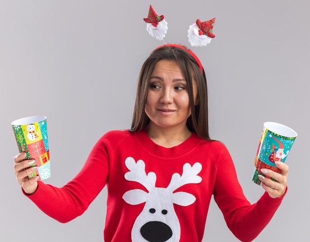 Giovane ragazza asiatica interessata che porta il cerchio dei capelli di natale con la tenuta del maglione e l'esame della tazza di natale isolata su fondo bianco