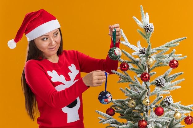 La giovane ragazza asiatica interessata che porta il cappello di natale con il maglione decora l'albero di natale isolato sulla parete arancione