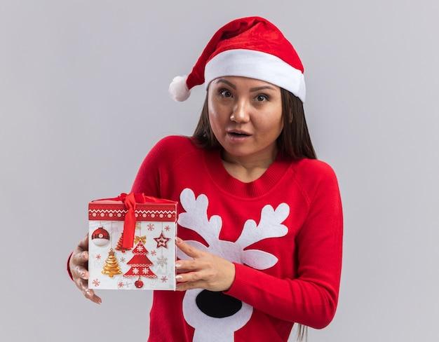 Обеспокоенная молодая азиатская девушка в новогодней шапке со свитером, держащая подарочную коробку на белом фоне