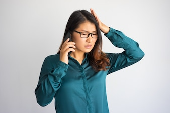 Concerned young Asian woman speaking on phone and touching head.