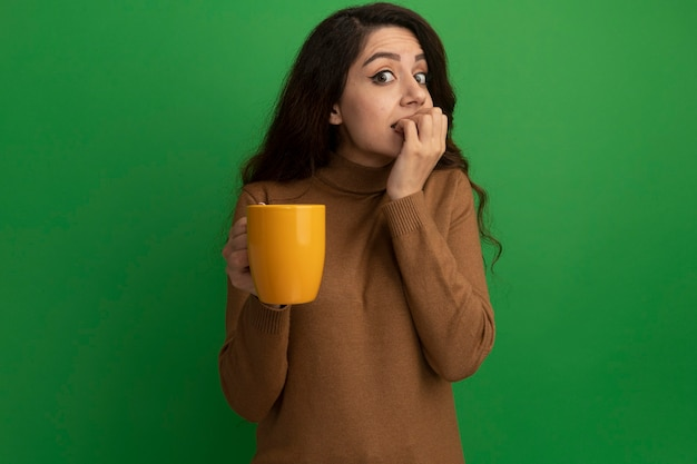 Concerned young beautiful girl holding cup of tea bites nails isolated on green wall
