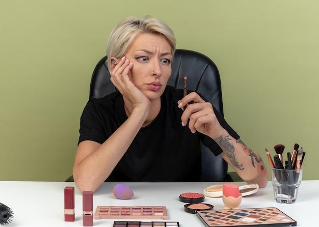 Обеспокоенная молодая красивая девушка сидит за столом с инструментами для макияжа, держа и глядя на кисть для макияжа, изолированную на оливково-зеленой стене