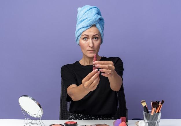 Обеспокоенная молодая красивая девушка сидит за столом с инструментами для макияжа, вытирая волосы полотенцем, протягивая помаду перед камерой, изолированной на синей стене