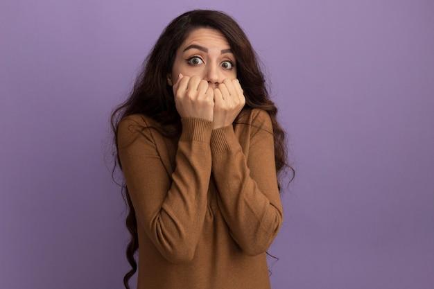 La giovane bella ragazza interessata che porta il maglione marrone del dolcevita ha coperto la bocca con le mani isolate sulla parete viola con lo spazio della copia