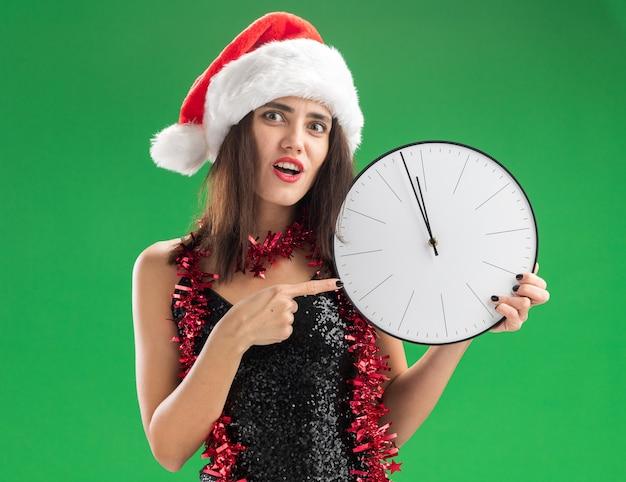 Giovane bella ragazza interessata che indossa il cappello di natale con la ghirlanda sulla tenuta del collo e indica l'orologio da parete isolato sulla parete verde